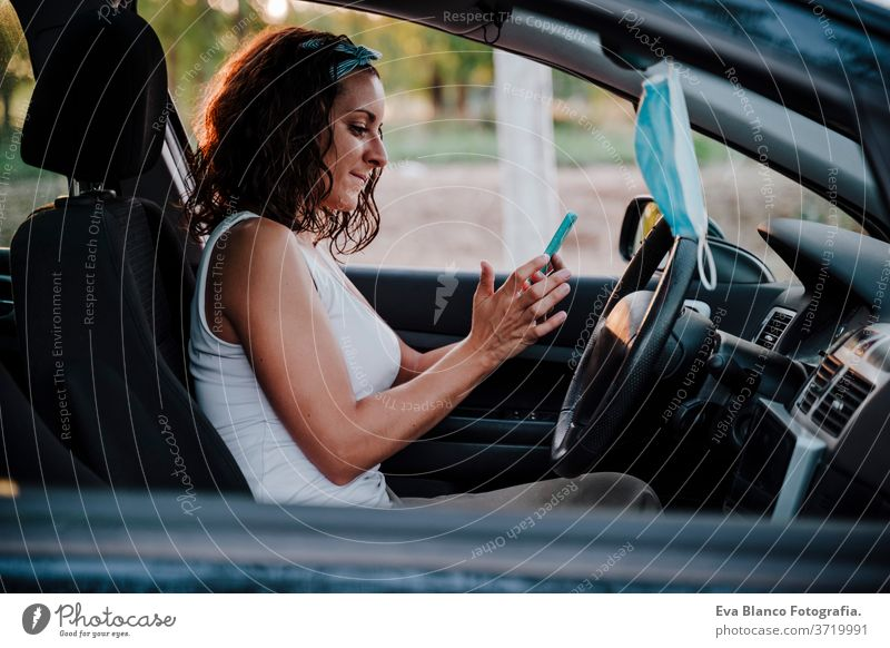 young woman in a car. Protective mask hanging from rear mirror. Travel and new normal concept protective mask driving corona virus travel pollen protection