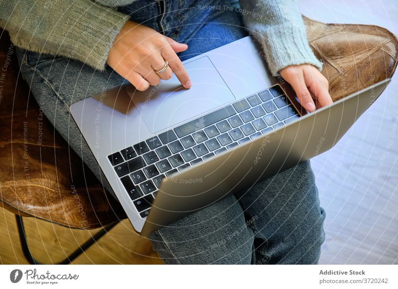 Woman working on laptop at home freelance remote woman typing project surfing using startup female cozy armchair internet gadget busy device browsing business