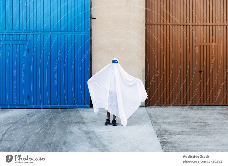 Anonymous kid in ghost costume in city halloween frighten child holiday entertain spooky autumn creepy scary event celebrate fall fantasy season street urban
