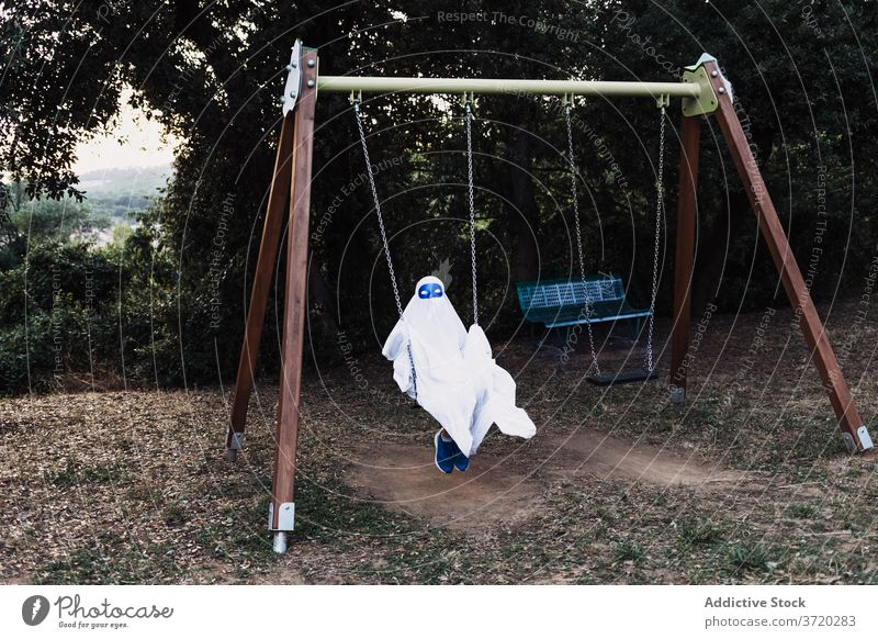 Child in ghost costume in yard halloween child play suit kid playground holiday autumn having fun event scary entertain spooky celebrate season fall creepy