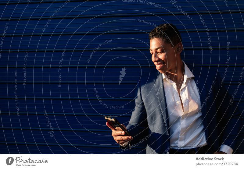 Cheerful businessman in formal suit browsing smartphone using happy success message cheerful read young african american ethnic black male manager elegant