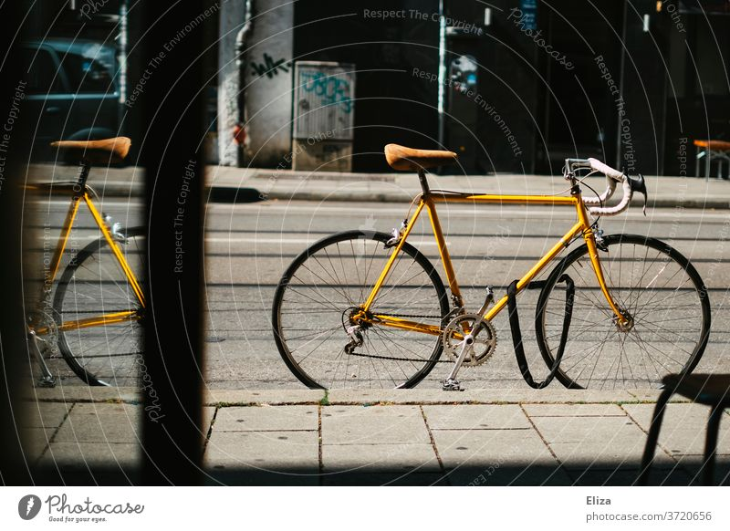 Yellow vintage road bike stands locked on the street in front of a shop Racing cycle completed bicycle lock Bicycle Cycling Retro Saddle leather saddle Sports