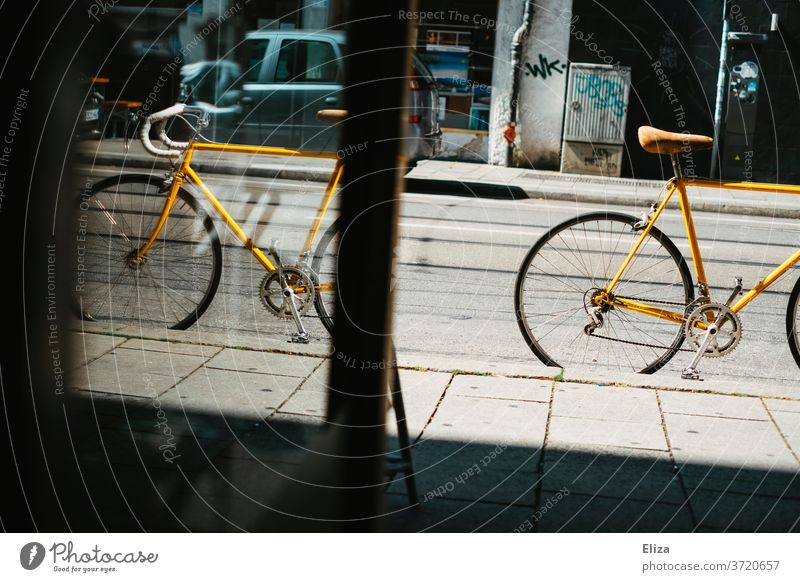 Yellow vintage road bike is on the street in front of a shop Racing cycle Bicycle Cycling Retro Saddle leather saddle Sports Lifestyle Hip & trendy Mobility hip