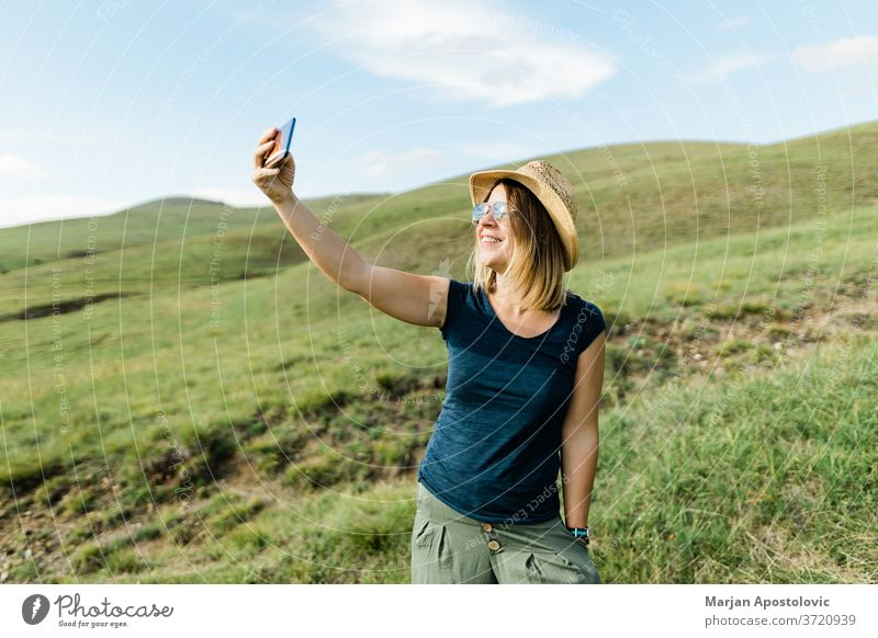 Young woman taking a selfie on hillside meadow in summertime adult adventure beautiful blog blogger blogging camera caucasian cheerful country cute enjoying