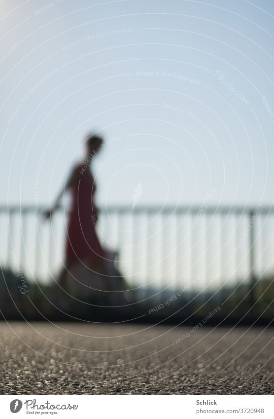 Young woman walks with bag in front of a railing over asphalt strong blur Woman Going Profile blurred Asphalt Sky Blue Dress Summer Handrail Back-light