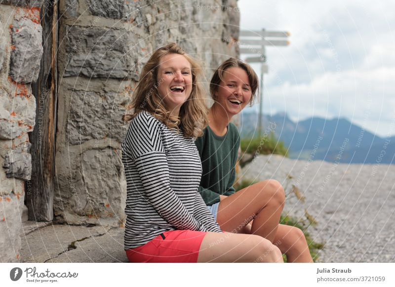 two young ladies are sitting laughing on the step in front of a stone house in the mountains Mountain hike Hiking Break take a break Laughter muck about fun Joy