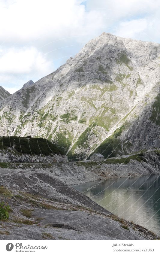 Lünersee in the mountains with small stone house on the reservoir Austria Hiking Visual spectacle Shadow Lonely splendid look-out Lakeside Reservoir Rock