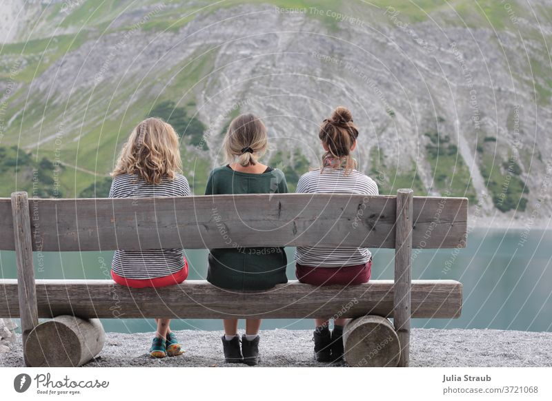 Three young women sitting on a rustic wooden bench at a mountain lake Hiking Break rest tranquillity Mountain Gray Stony Wooden bench Rustic Alpine petrol Lake
