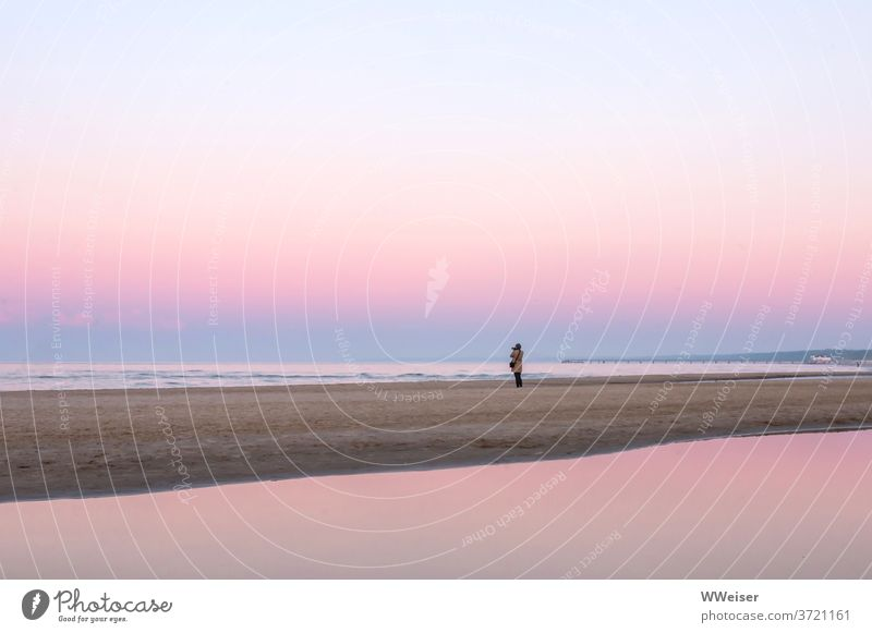 Photographer stands alone on the beach, romantic atmosphere prevails photo countess Beach Coast Sunset Pink pastel shades Smooth far silent Take a photo