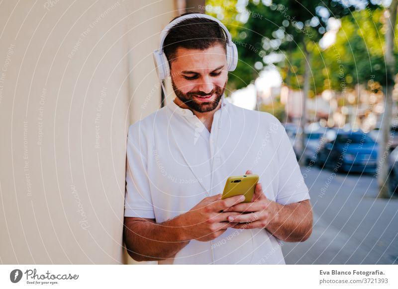 happy young man outdoors listening to music on mobile phone and headset. technology and lifestyle city urban smiling street modern beautiful summer using