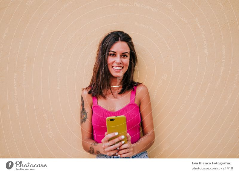 beautiful young woman outdoors taking a picture with mobile phone. Technology and lifestyle street urban smiling city technology tattoo modern happy summer