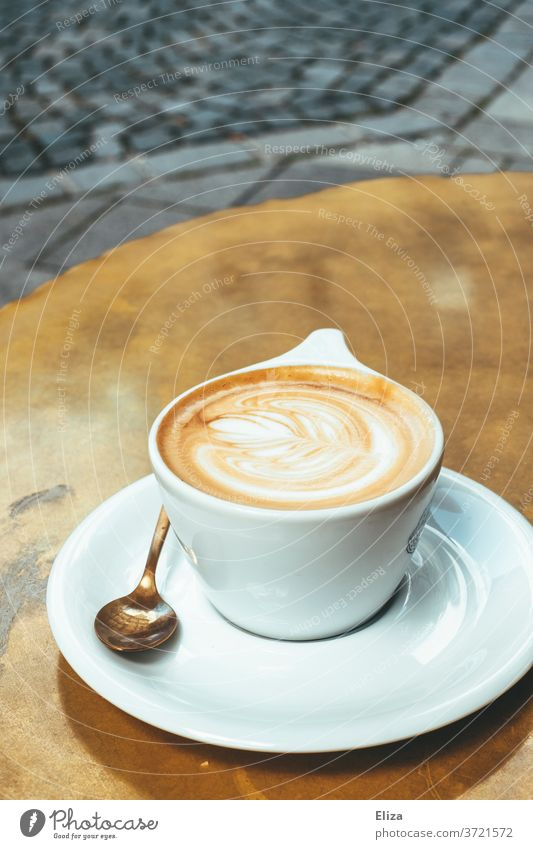 A cup of cappuccino on a golden table in the café Cappuccino Coffee Café Table latte type Cup Caffeine Beverage To have a coffee Coffee break Delicious warm