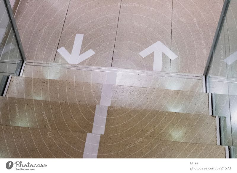 Directional arrows on the floor in front of a staircase. Setting the direction of movement in Corona times. Arrow running direction Stairs corona
