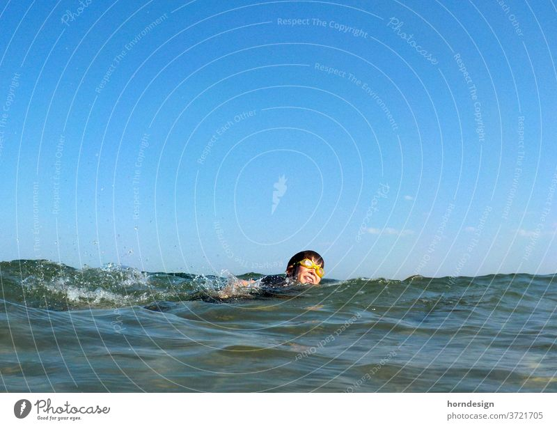 Boy swims in the sea Summer bathe be afloat Ocean Baltic Sea Summer vacation Swimming goggles Water Joy fun Sun holidays free time