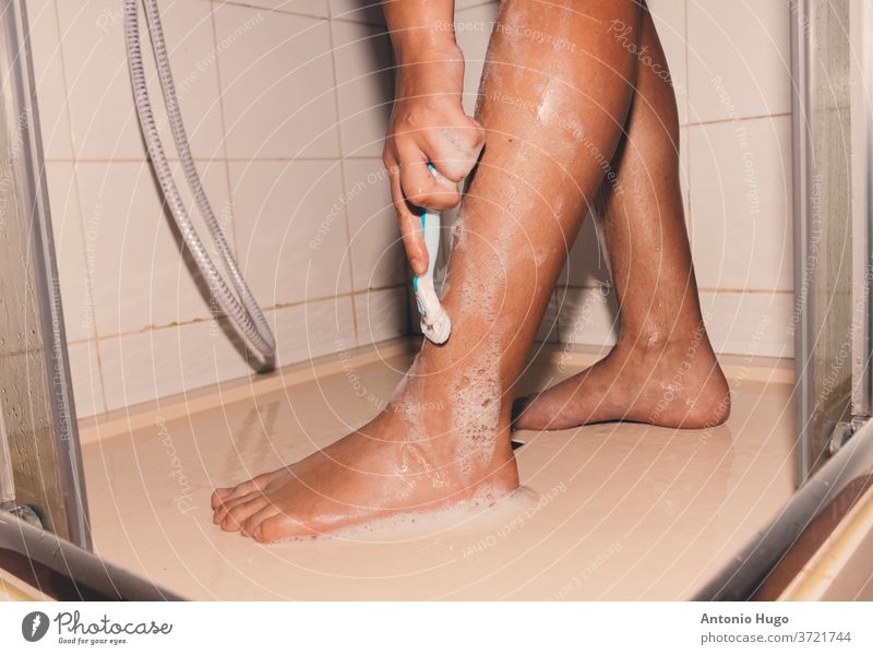 Woman shaving her legs with a razor blade in the shower. person woman hygiene female bathroom femininity spa body young alone bodycare cut out foam focused