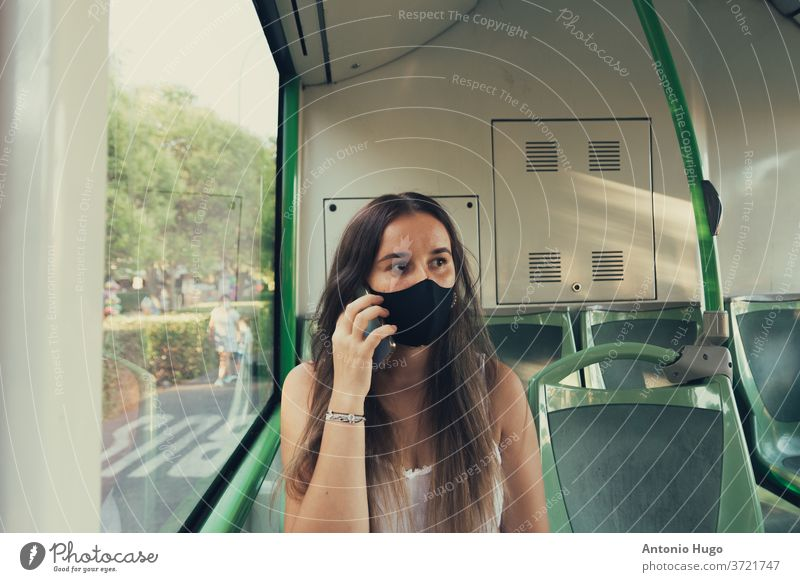 Girl with a face mask talking on her phone on the city bus medical virus person woman corona coronavirus covid epidemic pandemic transport health portrait
