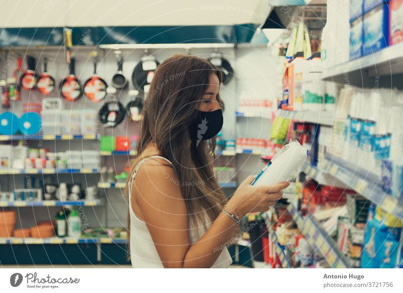 Girl with a face mask buying items at the supermarket. grocery coronavirus epidemic pandemic store supply woman budget checklist disease essential panic
