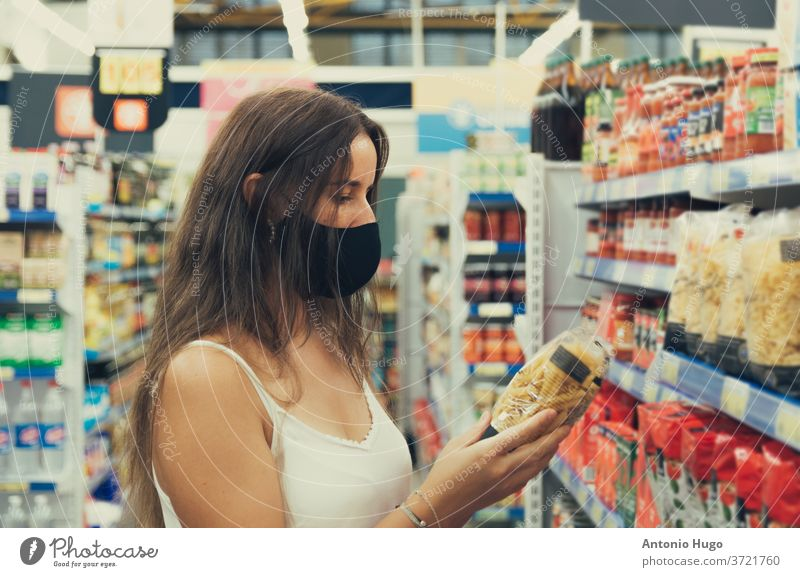 Girl with a face mask looking and buying items at the supermarket. grocery coronavirus epidemic pandemic store supply woman budget checklist disease essential