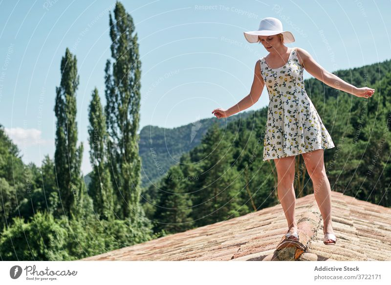 Calm woman standing on rooftop in summer relax mountain tranquil tile highland nature female sunlight summertime dress hat sunhat building enjoy vacation sit