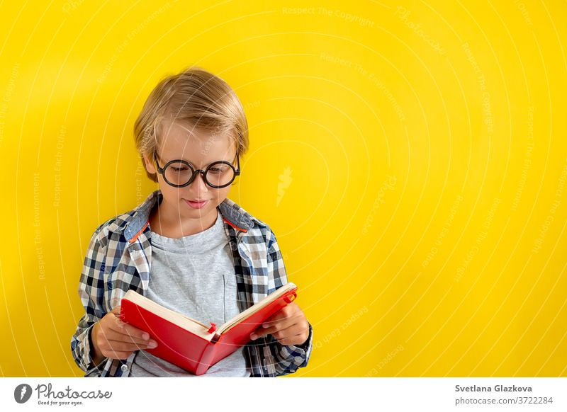 Portrait of cute and clever blonde Caucasian boy in a checked shirt on yellow background. 1 September day. Education and back to school concept. Child pupil ready to learn and study.