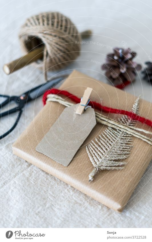 Gift christmassy wrapped on a linen tablecloth. Christmas & Advent Packaging Feasts & Celebrations White Studio shot Decoration Ornament Band Red Linen cloth