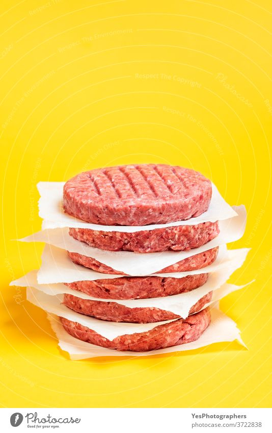 Burger patties stacked on the table. Raw beef patties isolated on yellow background. barbeque bbq burger butcher close-up comfort food cooking cow meat cuisine