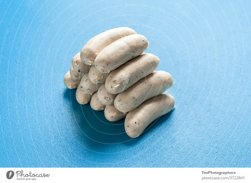 German white sausages stacked in a pile. Bavarian veal sausages. Cooked weisswurst Germany Oktoberfest aligned background bavarian blue boiled breakfast bunch