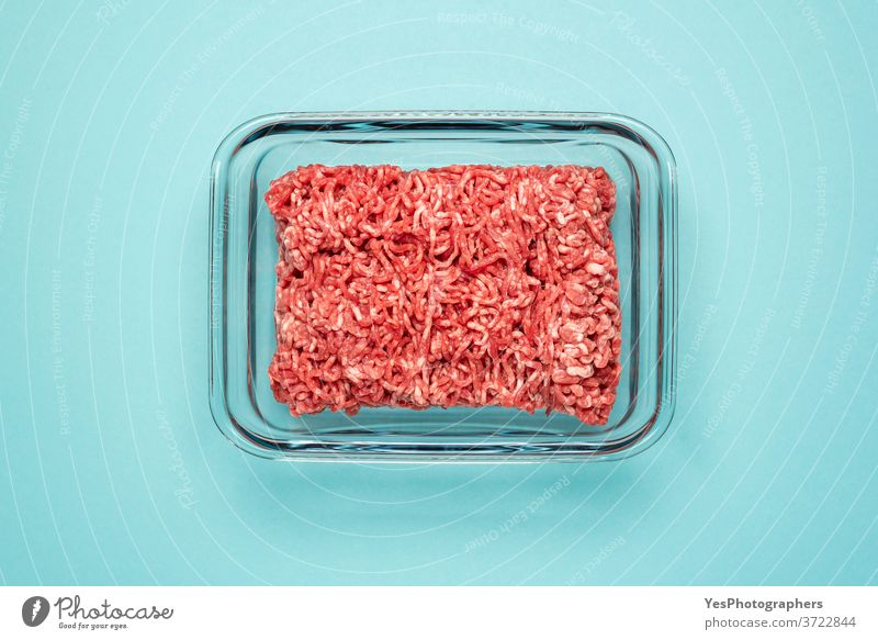 Raw beef in a glass food container. Ground meat in glass dish isolated on a colored background above view blue bowl box burger cooking cow meat cuisine culinary