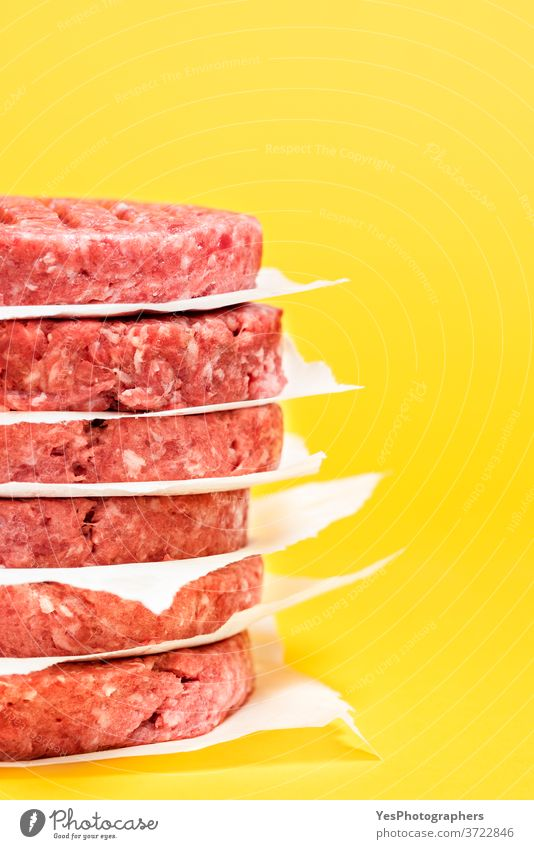 Raw beef patties close-up. Burger patties stacked against a yellow background. barbeque bbq burger butcher comfort food cooking cow meat cuisine culinary