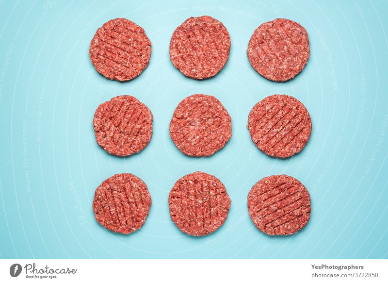 Raw hamburger patties isolated on blue background. Burger raw meat top view. above view aligned barbeque bbq beef butcher comfort food cooking cow meat cuisine