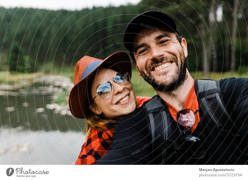 Selfie of a young couple in the mountains by the river 30s active adult adventure backpack backpackers backpacking boyfriend camera casual caucasian cheerful