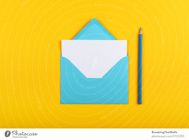 Open blue paper envelope over yellow Envelope one white sheet pencil wooden pastel vivid background closeup color colorful multicolor post mail message