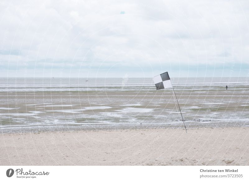 View of the North Sea and the mudflats at low tide on a cloudy windy day. Three tidal flat hikers are on their way. On the beach a black and white flag is in the foreground.