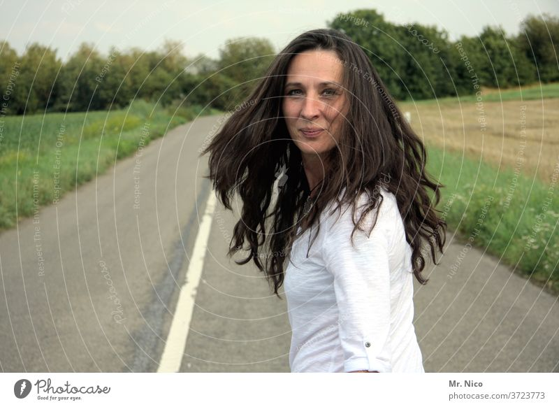 Woman with long flowing hair looks into the camera Hair and hairstyles Movement Street Lanes & trails Feminine smile Spirited Swing Good mood Spontaneous