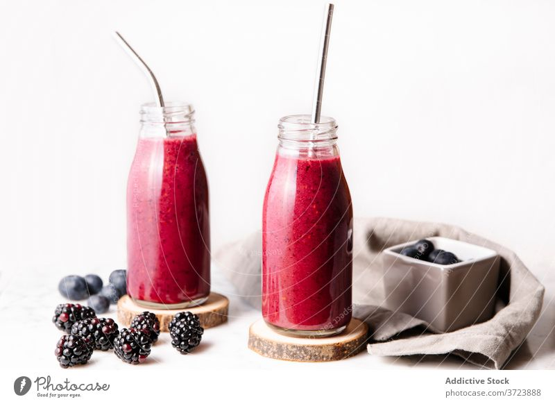 Berry smoothie in glass bottles with reusable metal straws. Front shot with white background. Bottle Color Drink Food and drink Fruits Gastronomy Glass bottle