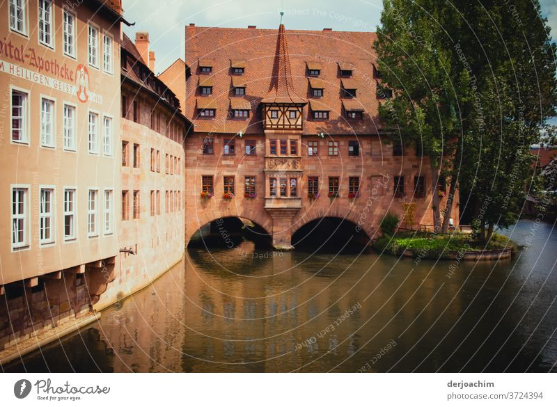Hospital pharmacy Nuremberg, architecture in old style . A river flows through the building. There beside stands a tree. Franconia Architecture Building