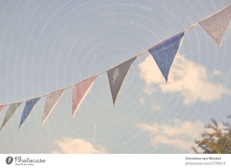 self-sewn pennant chain made of colourful fabrics in the sunlight against a slightly cloudy blue sky Self-made Cloth Cloth pattern Sun Sky Clouds Blue