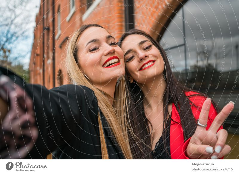 Two young friends taking a selfie outdoors. portrait two cheerful street adult hangout girls travel woman urban leisure joy style cool enjoyment positive