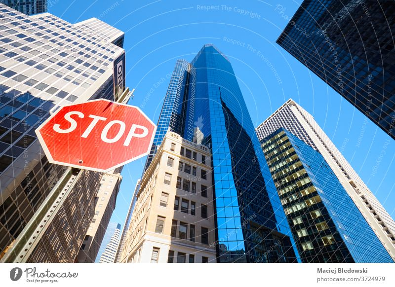Looking up at stop sign on a street of New York City, USA. city look up nyc office building business Manhattan skyscraper warning traffic sign window red