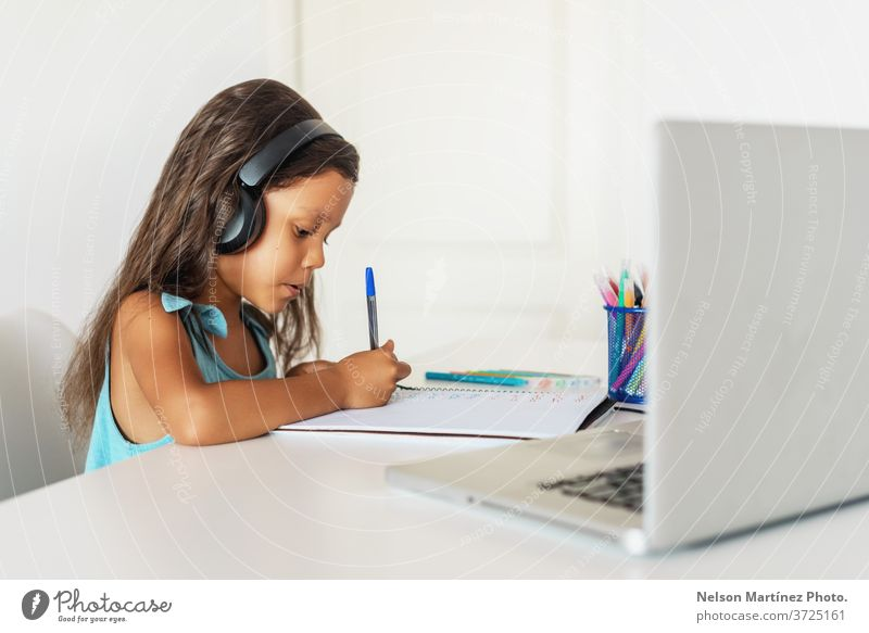 Little hispanic girl studying in front of the laptop. E-learning, study at home online. computer children young video school education e-learning technology