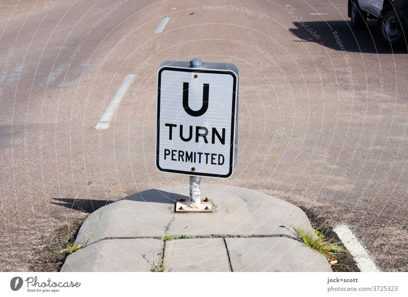 U-turn permitted Turnaround allowed hairpin bend Street Street refuge Asphalt Traffic infrastructure Road sign car shadow Lane markings Car Sunlight Calm Word