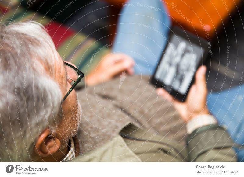 Senior man using an ebook reader adult alone break caucasian closeup device digital e-book enjoying senior hands hold home house indoor inside interior leisure