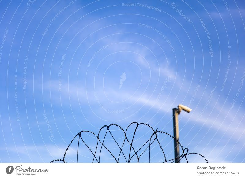 Security camera behind barbed wire fence on the prison wall danger border sky jail camp razor protection security crime surveillance blue metal closeup boundary