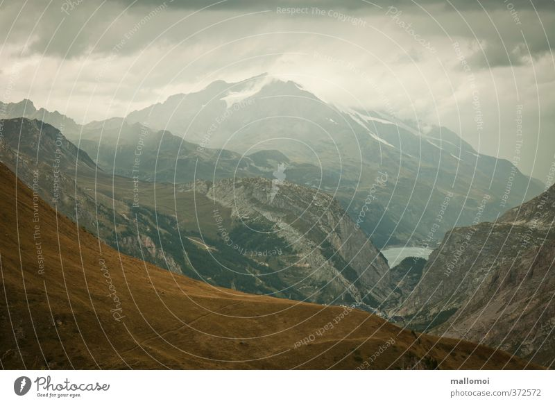 alpine panorama Environment Nature Landscape Elements Sky Clouds Storm clouds Bad weather Rain Rock Alps Mountain Peak Threat Blue Brown Gray Loneliness Respect