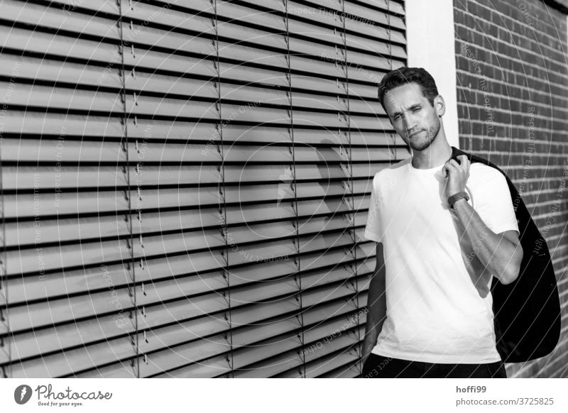 young man with jacket in front of closed blinds Young man Masculinity Manly Face of a man portraite relaxed Fashion Facial hair Contrast Looking into the camera