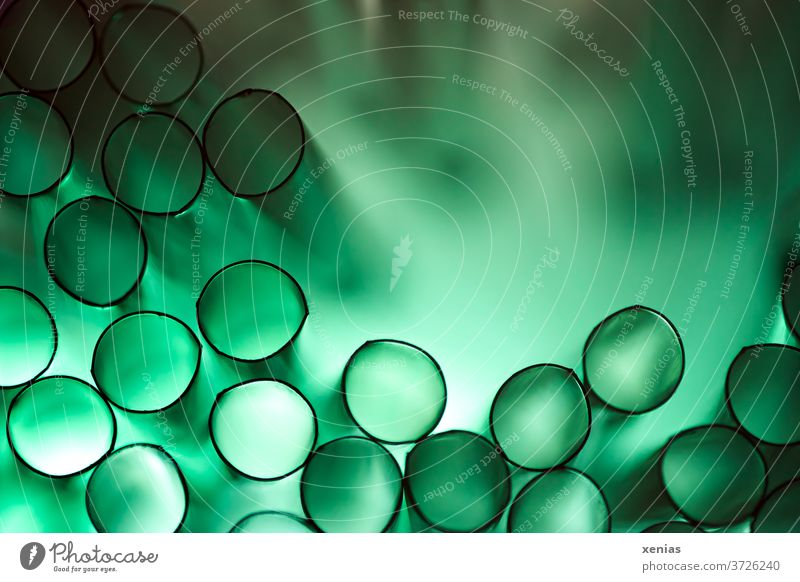 Green plastic drinking straws with light produce black circles with green background Drinking straws Structures and shapes Macro (Extreme close-up) Detail