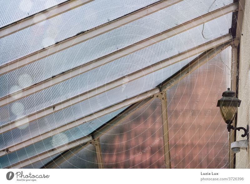 An old-fashioned glass roof and a yellow lamp, with shimmering raindrops Canopy Glass roof Lamp Entrance Gloomy Old nostalgically Morbid Roof Roofing tile Light