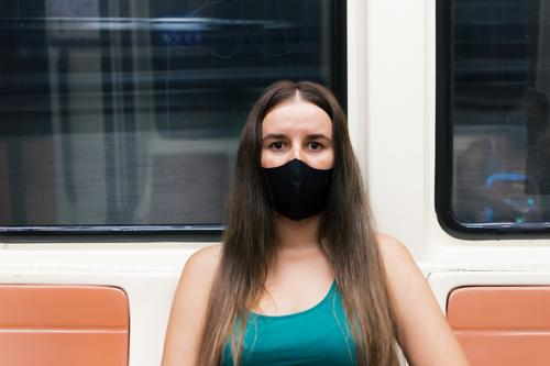 Serious young blonde woman wearing a protective mask against the virus sitting on the subway seat. person train epidemic pandemic bokeh coronavirus flu medical