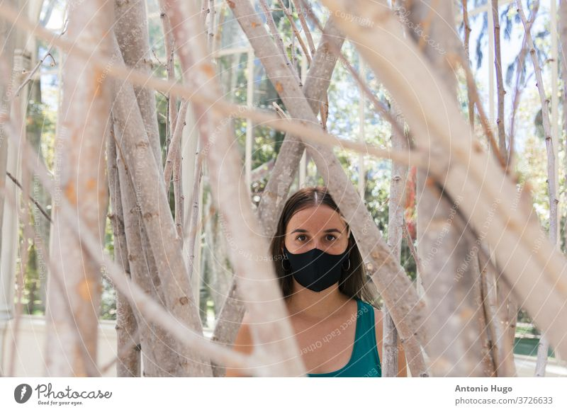 Portrait of a young blonde woman with a protective mask against the virus. Tree background. trees portrait madrid masked corona wearing person epidemic