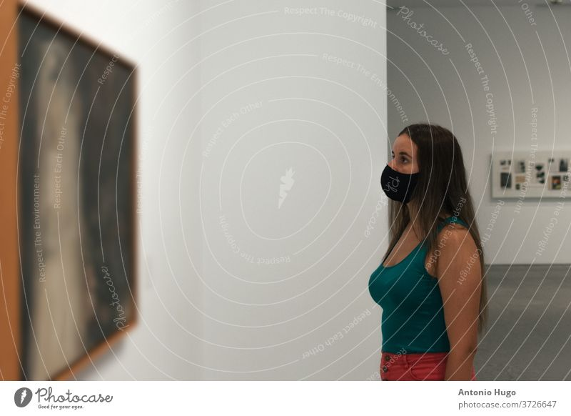 Young blonde woman in a virus mask looking at a famous painting in the museum. person corona gallery visit exhibition art collection interesting visitor young